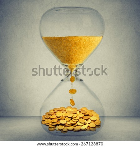 Time is money financial opportunity concept. Sand clock with gold dust and coins isolated on gray wall background  - stock photo