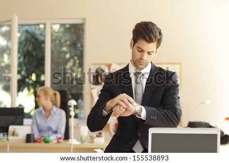Time is money. Handsome businessman looking at his watch in office. Shallow focus.