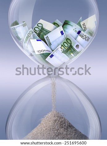 Time is money. Hourglass filled with bills of one hundred euros. Symbolizes time business processes. - stock photo