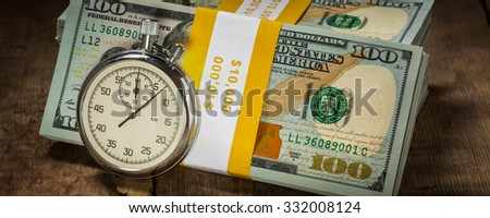 Time is money loan concept background -  letterbox panorama of stopwatch and stack of new 100 US dollars 2013 edition banknotes (bills) bundles on wooden background - stock photo