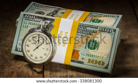 Time is money loan concept background - panorama of stopwatch and stack of new 100 US dollars 2013 edition banknotes (bills) bundles on wooden background - stock photo