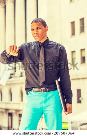 Time is Money. Ready to work. Serious African American businessman standing on street in New York, carrying laptop computer, looking at his wristwatch, waiting for you to meet. Instagram effect. - stock photo