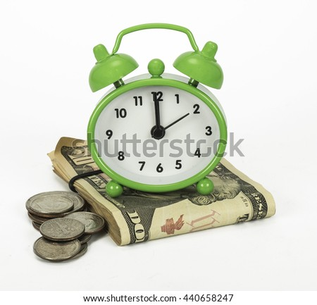 Time is money represented by a green vintage style alarm clock on a stack of folded bills and various silver coins against a white background.