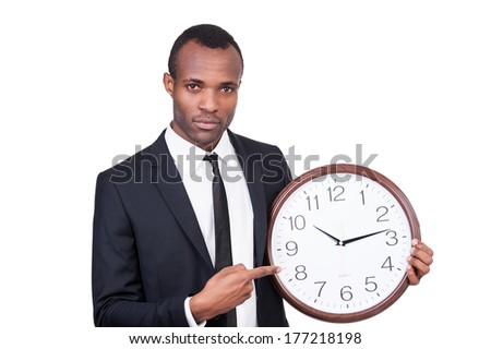 Time is money! Serious young African man in formalwear holding a clock in his hand and pointing it while standing isolated on white background  - stock photo