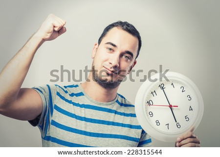 Time is money! Serious young man holding a clock in his hand
