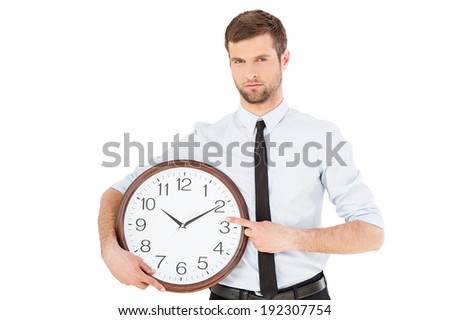 Time is money! Serious young man in formal wear holding a clock in his hand and pointing it while standing isolated on white background