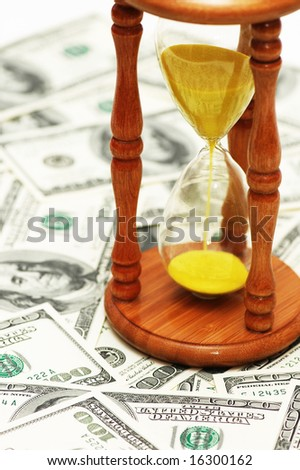 Time is money with dollar notes and  hourglass - stock photo