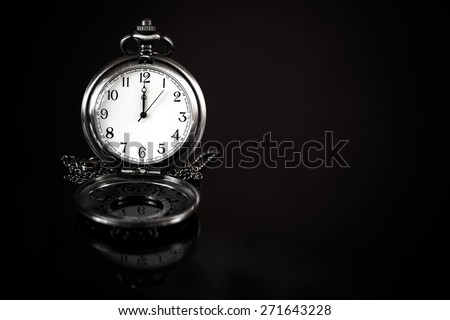 time is precious concept, pocket watch over a black background - stock photo