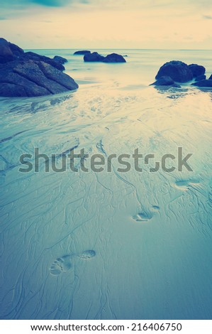 Time-lapse of beach at dusk with footprints in sand with Instagram style filter - stock photo
