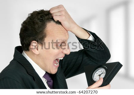Time-management concept: business man looking at clock is shocked - stock photo
