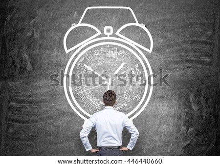 Time management concept with thoughtful businessman looking at chalkboard wall with alarm clock sketch - stock photo