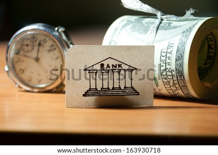 Time, money, bank concept. watches, bank, roll of banknotes. - stock photo