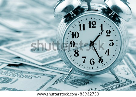 Time - money. Business concept. Analog hours on a heap of paper dollars. Blue tone - stock photo