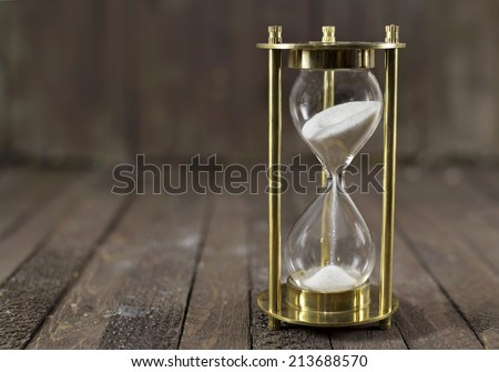 Time passing. Sand clock on wooden background - stock photo
