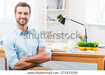 Time to be productive. Handsome young man in shirt keeping arms crossed and smiling at camera while sitting at his working place - stock photo
