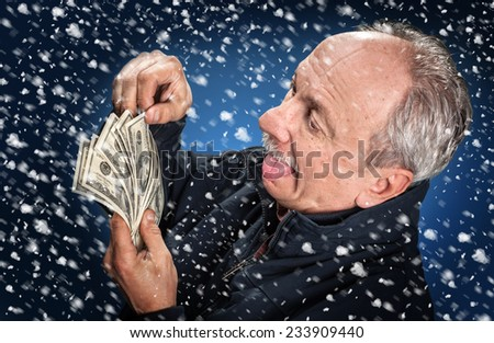 Time to buy gifts. Portrait of a man with a bundle of dollars on a blue background in snowfall - stock photo