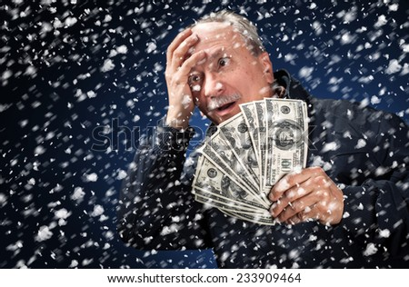 Time to buy gifts. Portrait of a man with a bundle of dollars on a blue background in snowfall, Focus on money - stock photo