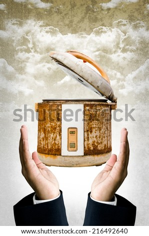Time to change your rice cooker concept, Old rice Cooker in businessman hand - stock photo