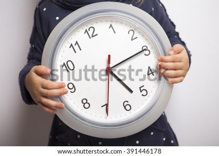 Time to come back home. Child holding clock which shows after five. - stock photo