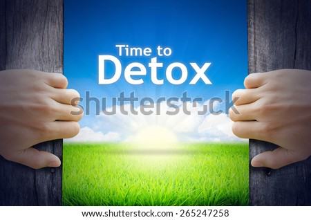 Time to Detox. Hands opening a wooden door then found a texts floating among new world as green grass field, Blue sky and the Sunrise. - stock photo