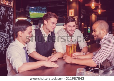 Time to drink beer. Four friends drinking beer and having fun together in the bar
