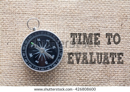 Time to Evaluate written on burlap background with compass,Conceptual - stock photo