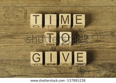 time to give text on a wooden cubes on a wooden background