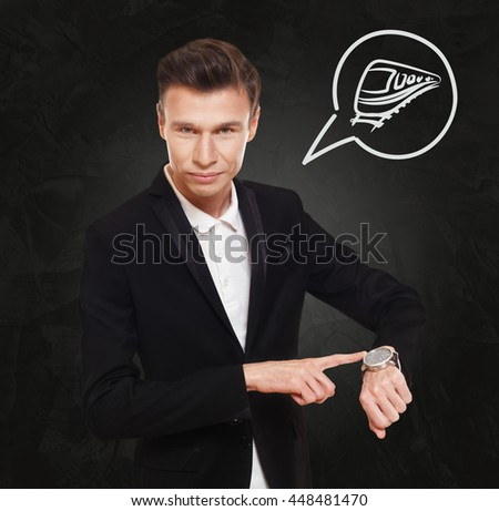 Time to go. Businessman point at his hand watch showing clock. Man in suit at black background, thinking cloud with train symbol. Travel departure, late at railway station for business trip