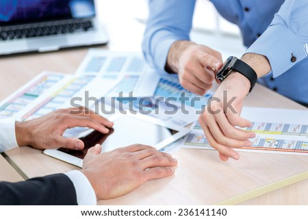 Time to go into business. Confident businessman pointing at his watch. Close-up view of the hands of a businessman in the office of the table in the formal wear. - stock photo