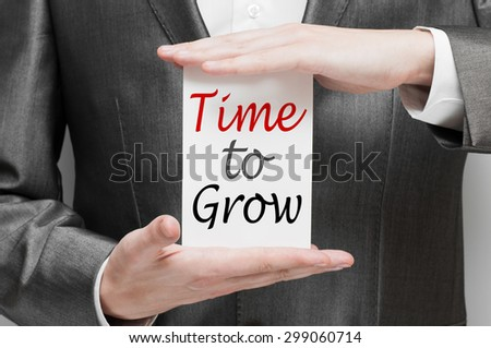 Time to Grow card in hands of businessman - stock photo