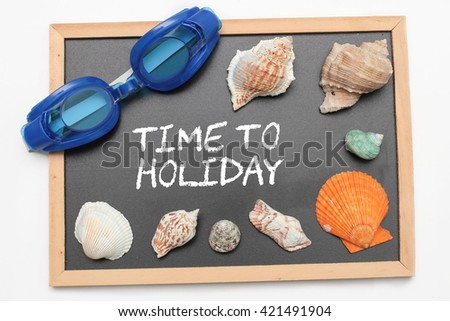 Time to Holiday text on chalk board with swimming goggle and shell - vacation and business concept - stock photo
