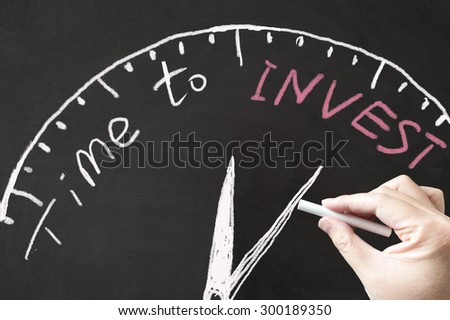 Time to invest words and clock sign drawn on blackboard using chalk - stock photo