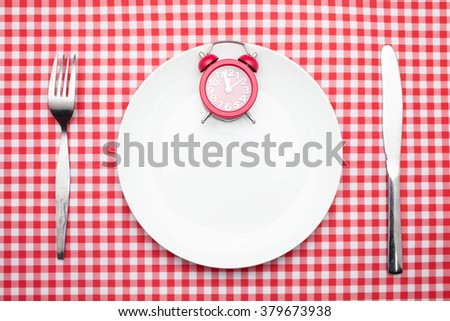 Time to lunch Concept : 12 o'clock Red Clock on white dish,knife and fork on red checker table cloth - stock photo