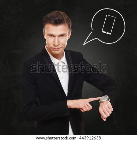 Time to make a call. Businessman in suit points at his watch at black background, thinking cloud with cell phone symbol. Modern mobile device, smartphone communication concept - stock photo