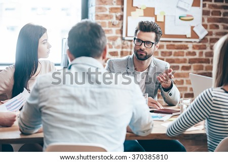 Time to make new business decisions. Young handsome man wearing glasses gesturing and discussing something while his coworkers listening to him sitting at the office table - stock photo