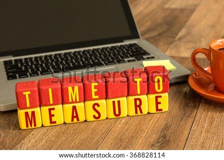 Time To Measure written on a wooden cube in a office desk - stock photo