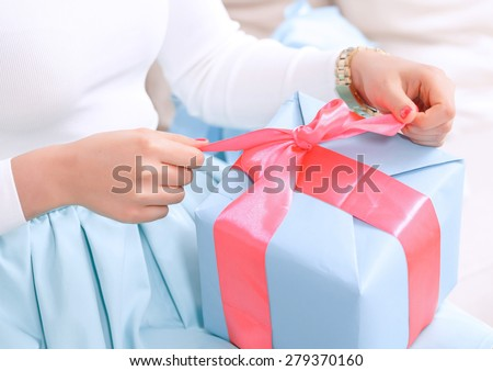 Time to open presents. Close up hands of a girl pulling a red ribbon to open her birthday gift in a blue box - stock photo