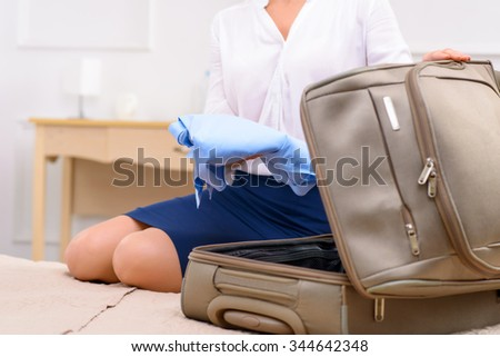 Time to pack. Young woman is sitting on bed and packing her bag. - stock photo