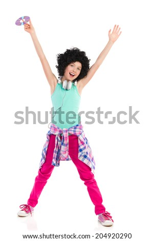 Time to party! Teen girl in afro wig holding compact disc with arms outstretched. Three quarter length studio shot isolated on white. - stock photo