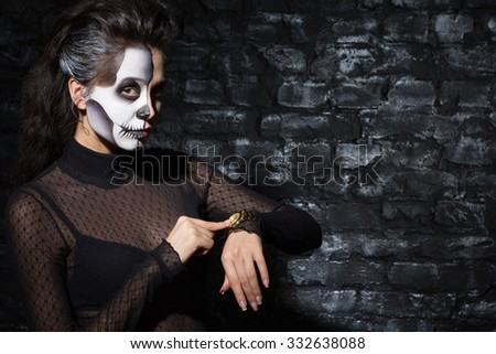 Time to party. Waist up portrait of a beautiful woman with skeleton body art on her face pointing at the watches meaning she is ready with her Halloween make up, in a dark room - stock photo