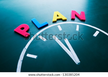 Time to plan concept, color word and clock on blackboard - stock photo