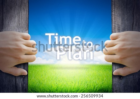 Time to Plan . Hand opening an old wooden door and found Time to Plan word floating over green field and bright blue Sky Sunrise. - stock photo
