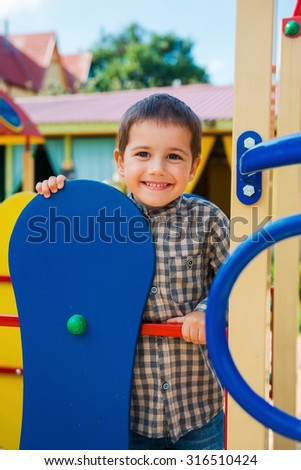 Time to play. Happy little boy looking and camera and smiling while having fun on jungle gym - stock photo