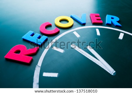 Time to recover concept, color word and clock on blackboard - stock photo