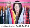 Time to refresh wardrobe young attractive surprised woman searching for clothing in a closet  - stock photo