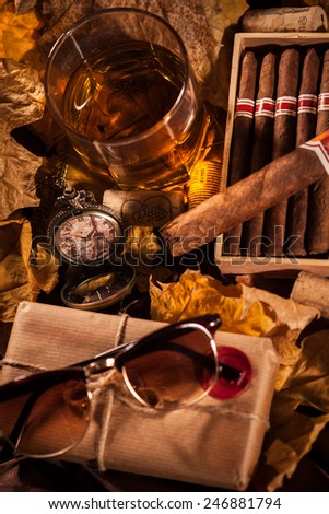 Time to relax! A complete set of male pleasures: a glass of whiskey, havana cigars in open humidor box, sunglasses and pocket watch in memory of a trip to Paris - stock photo