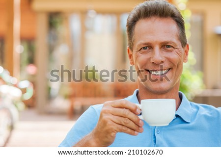 Time to relax. Cheerful mature man drinking coffee and smiling while sitting outdoors with house in the background  - stock photo