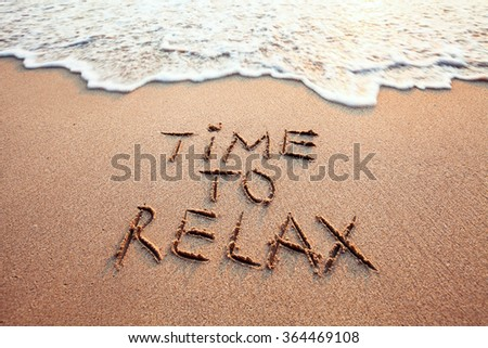 time to relax, concept written on sandy beach - stock photo