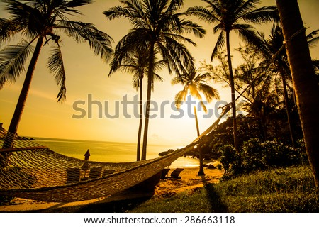 Time to relax with silhouette of hammock and coconut tree at the beach on sunset time in Samui Island Thailand - stock photo