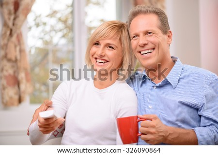 Time to rest. Overjoyed adult smiling couple bonding to each other and holding remote control while watching TV - stock photo